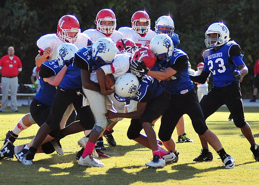 Polk Middle's defense swarms a Hendersonville runner.